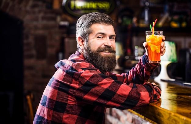 Vrolijke bebaarde man, cocktails drinken en glimlachen. tropische alcoholische verse cocktail.