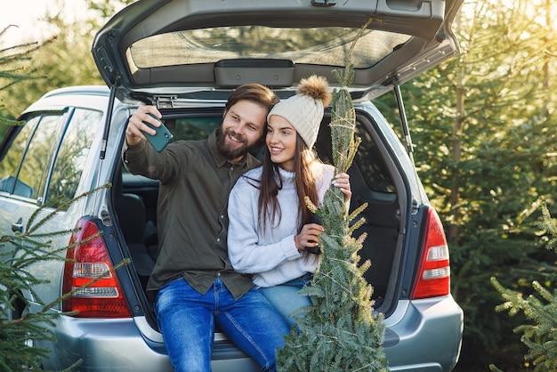 Vrolijke bebaarde man en mooie vrouw in hoed selfie foto zitten in auto kofferbak met fir tree op plantage gebied maken.