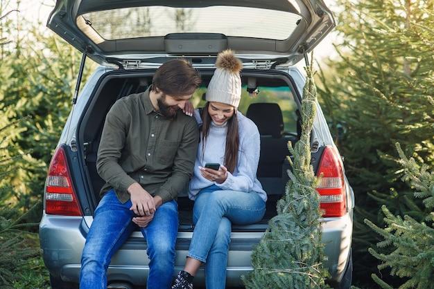 Vrolijke bebaarde man en mooie vrouw in hoed zitten in auto kofferbak fir tree te houden en te gebruiken