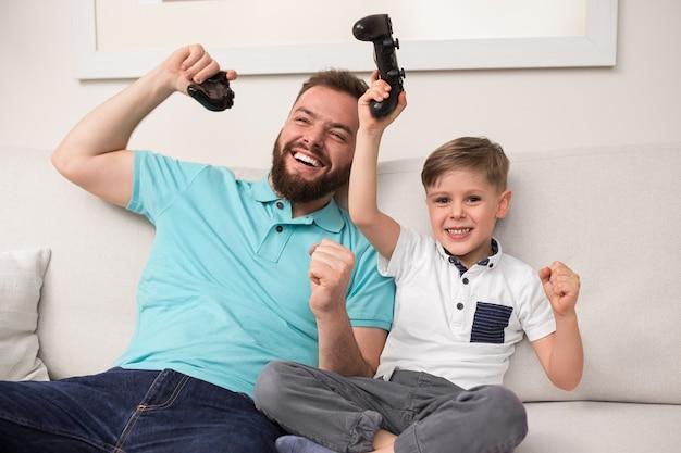 Vrolijke bebaarde man en zoontje met gamepads in opgeheven handen vieren de overwinning terwijl ze thuis samen videogame spelen