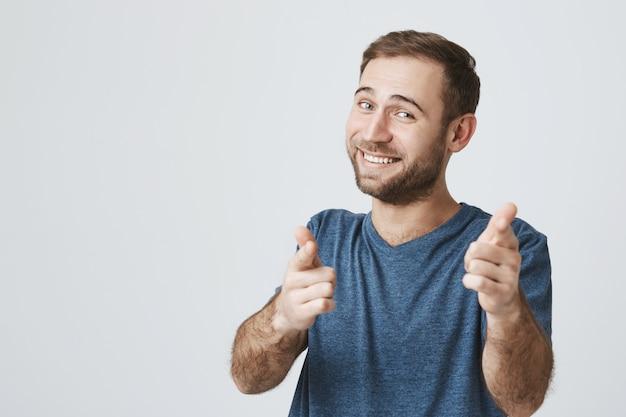 Vrolijke bebaarde man feliciteren u, wijzende vingers camera