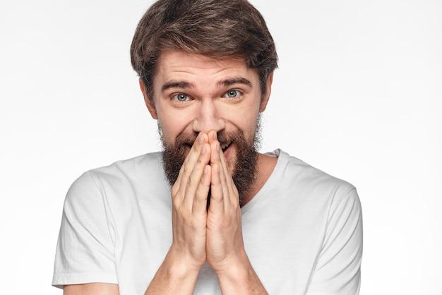Vrolijke bebaarde man in een wit t-shirt emoties gebaren met zijn handen lichte studio.
