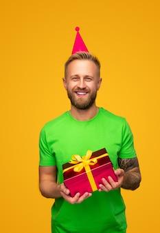 Vrolijke bebaarde man in groen shirt en rode feestmuts glimlachend voor camera en uitvoering van geschenkdoos tijdens verjaardagsviering tegen geel
