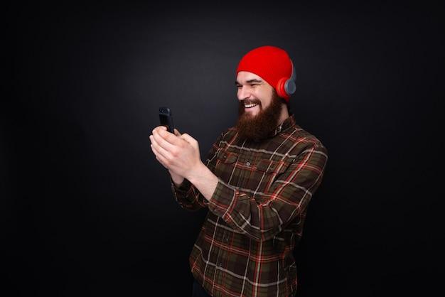 Vrolijke bebaarde man in koptelefoon luisteren van muziek en kijken op smartphone