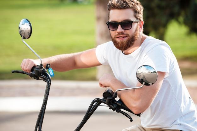 Vrolijke bebaarde man in zonnebril zittend op moderne motor buitenshuis en kijken naar de camera
