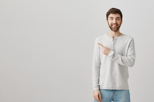 Vrolijke bebaarde man naar links wijzend op advertentie