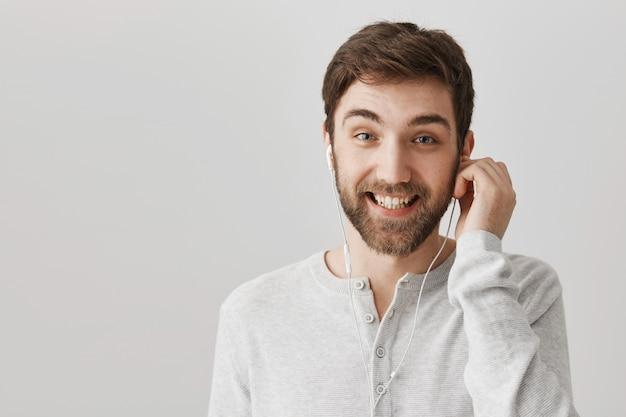 Vrolijke bebaarde man oortelefoons zetten om naar muziek te luisteren