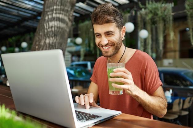 Vrolijke bebaarde man sociale afstand met vrienden, videobellen met laptop zittend op terras
