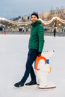 Vrolijke bebaarde man staat in de buurt van skatehulp, gaat voor de eerste keer skaten en is in een goed humeur