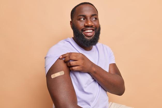 Vrolijke bebaarde man toont schouder met plakband na vaccinatie ontvangen coronavaccin beige muur
