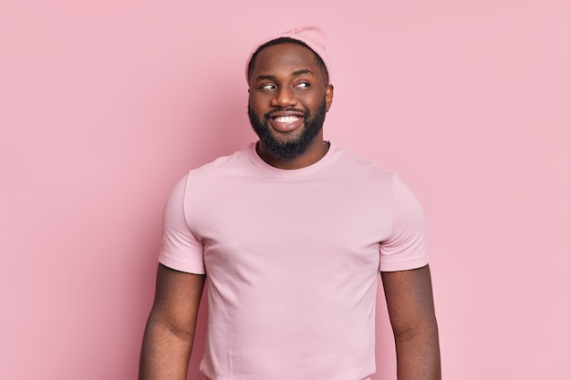 Vrolijke, bebaarde zwarte man glimlacht broady kijkt nieuwsgierig opzij heeft witte gelijkmatige tanden draagt hoed en t-shirt in één toon met muur