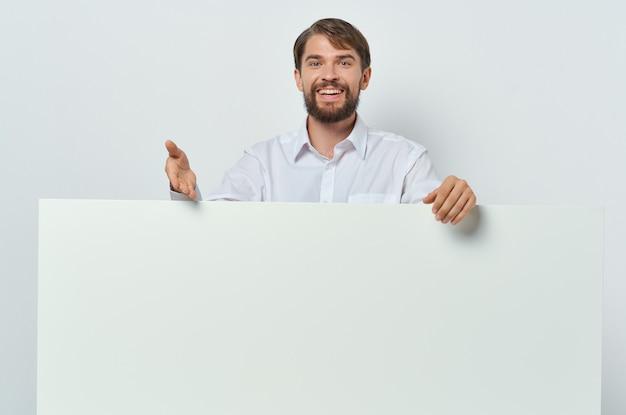 Vrolijke bedrijfsmens die in overhemd wit reclamebord houdt