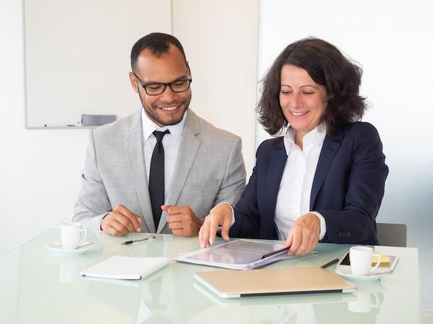 Vrolijke bedrijfsmensen die contract ondertekenen