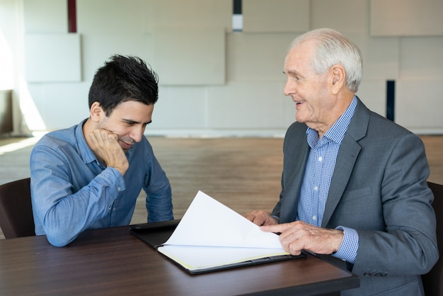 Vrolijke bedrijfsmensen die document bespreken