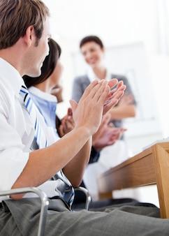 Vrolijke bedrijfsmensen die een goede presentatie toejuichen