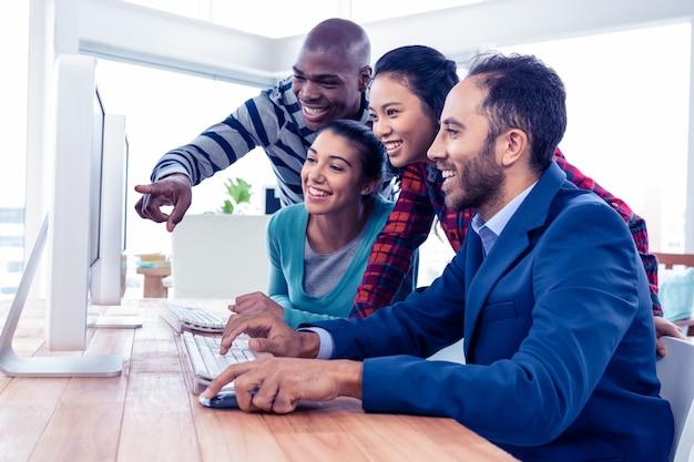 Vrolijke bedrijfsmensen die het computerscherm in creatief bureau bekijken