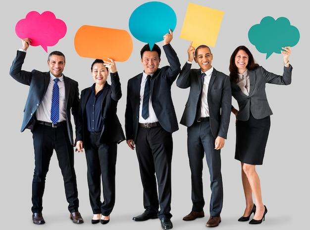 Vrolijke bedrijfsmensen die pictogram van de toespraakbel houden