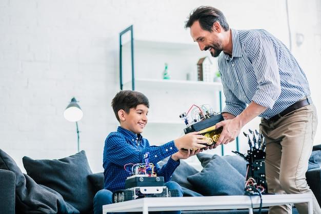 Vrolijke behulpzame vader en zijn slimme zoon die een robotapparaat vasthouden terwijl ze samen een technisch project voorbereiden