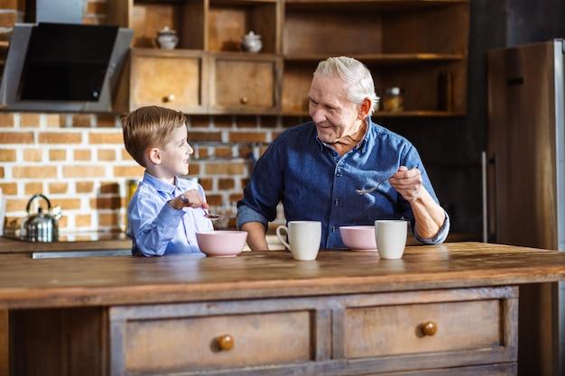 Vrolijke bejaarde en zijn kleinzoon die granen eten terwijl ze genieten van hun ochtend