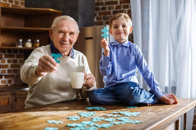 Vrolijke bejaarde man en zijn kleine schattige kleinzoon die puzzels in de keuken samenstellen