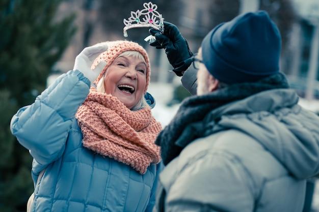 Vrolijke bejaarde vrouw die lacht terwijl ze in winterkleren staat en man die een schattige tiara op haar hoofd zet