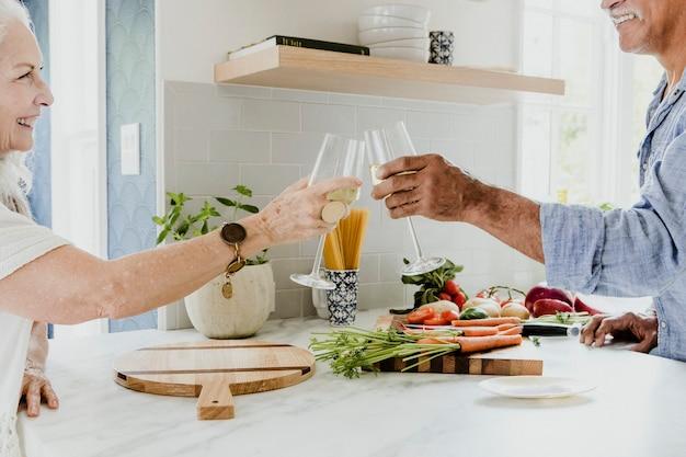 Vrolijke bejaarden die hun witte wijn rammelen in een keuken