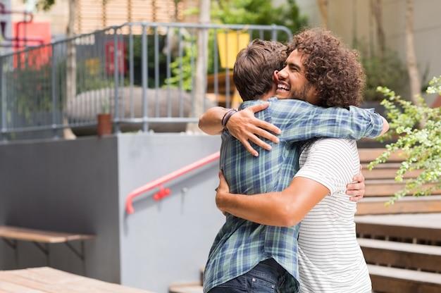 Vrolijke beste vrienden die elkaar buiten coffeeshop omhelzen