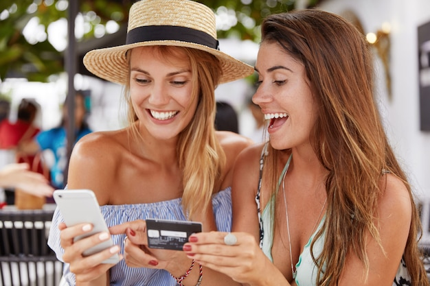 Vrolijke beste vriendenvrouwen ontmoeten elkaar in cafetaria, graag online winkelen met smartphone en plastic kaart