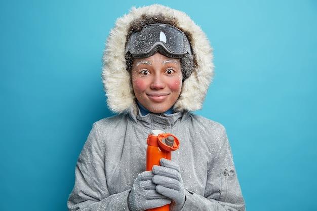 Vrolijke bevroren vrouw met rood gezicht tijdens vorst glimlacht aangenaam heeft koffiepauze na snowboarden activiteit draagt warme winterkleren houdt thermoskan met warme drank.