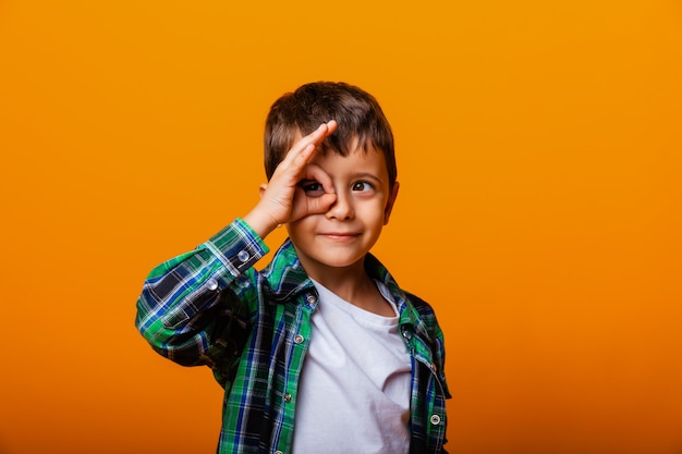 Vrolijke blanke jongen hand in hand in de buurt van gezicht in de vorm van een masker, geïsoleerd op gele achtergrond.