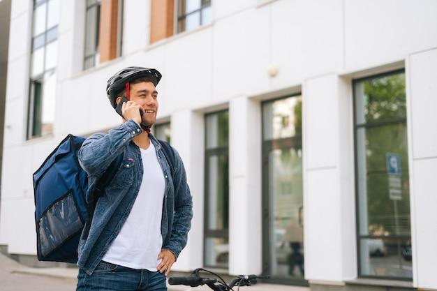 Vrolijke blanke koeriersman met thermische rugzak die op mobiele telefoon praat met klant, op zoek naar adres om online bestelling te bezorgen. bezorger in beschermende helm die smartphone buitenshuis gebruikt.