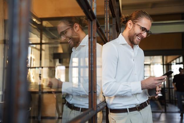 Vrolijke blanke man in bril die lacht en mobiele telefoon gebruikt terwijl hij op een glazen wand op kantoor leunt