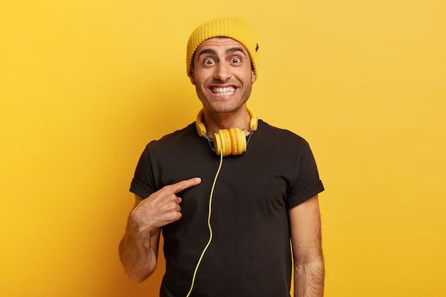 Vrolijke blanke man met donkere ogen wijst vrolijk naar zichzelf, tevreden met een leuke suggestie, draagt een zwart t-shirt