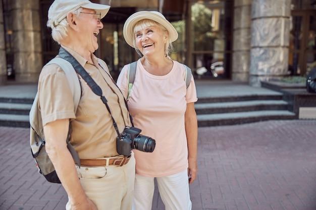 Vrolijke blanke mannelijke gepensioneerde met een digitale camera en zijn vrolijke vrouw die hartelijk buiten lacht