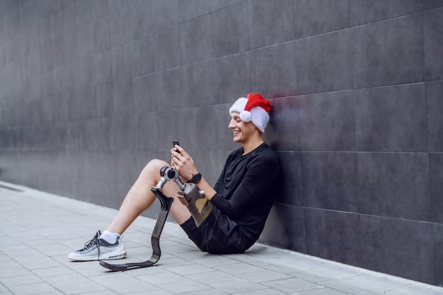 Vrolijke blanke sportman met kunstbeen en met kerstmuts op hoofd zittend op de grond, leunend op de muur en het verzenden van wensen voor kerstmis via zijn slimme telefoon.