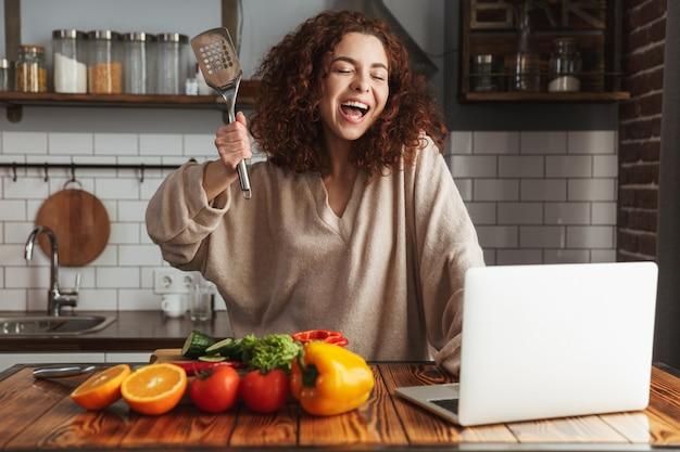 Vrolijke blanke vrouw die laptop gebruikt tijdens het koken van verse groentesalade in het keukeninterieur thuis