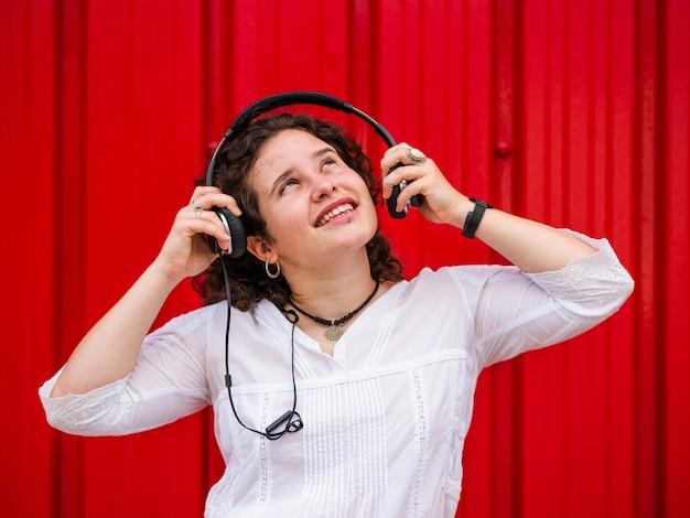 Vrolijke blanke vrouw die naar muziek luistert met een koptelefoon op rode achtergrond