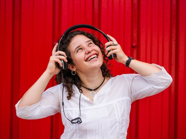 Vrolijke blanke vrouw die naar muziek luistert met een koptelefoon op rode scène