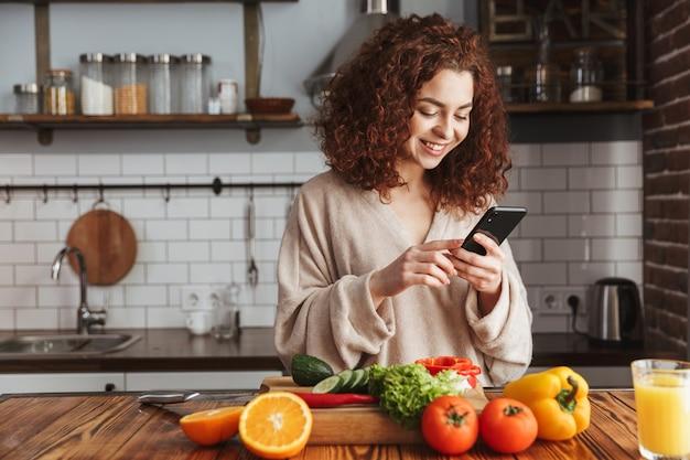 Vrolijke blanke vrouw die smartphone vasthoudt tijdens het koken van salade met verse groenten in het keukeninterieur thuis