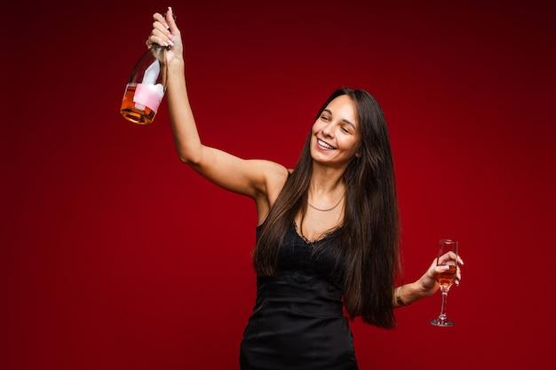Vrolijke blanke vrouw met een aantrekkelijk uiterlijk met een fles champagne en glas, foto op rood