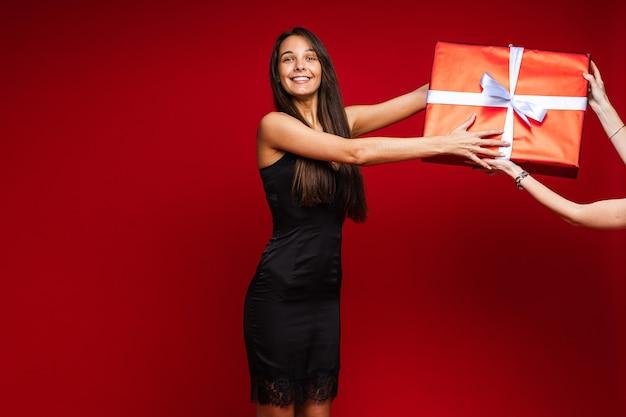 Vrolijke blanke vrouw met een aantrekkelijk uiterlijk met een grote doos met een cadeautje, foto op rood