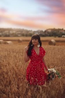 Vrolijke blanke vrouw met golvend lang donker haar in rode jurk met een tas en bloemen in haar handen