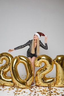 Vrolijke blanke vrouw met lang blond haar viert het nieuwe jaar 2021 met veel gouden confetti en een glas champagne