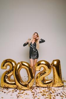 Vrolijke blanke vrouw met lang blond haar viert het nieuwe jaar 2021 met veel gouden confetti