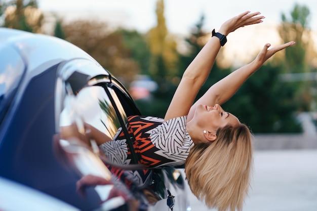 Vrolijke blanke vrouw rijdt door de pittoreske zonnige stad en zwaait met haar armen terwijl ze zich op een mooie dag uit het autoraam uitstrekt