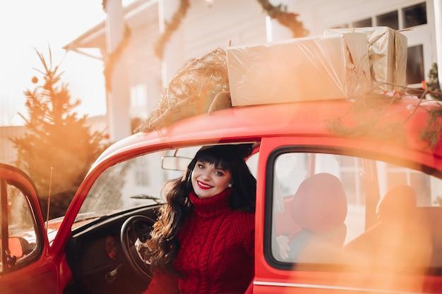 Vrolijke blanke vrouw zit in de bestuurdersstoel van de auto en glimlacht