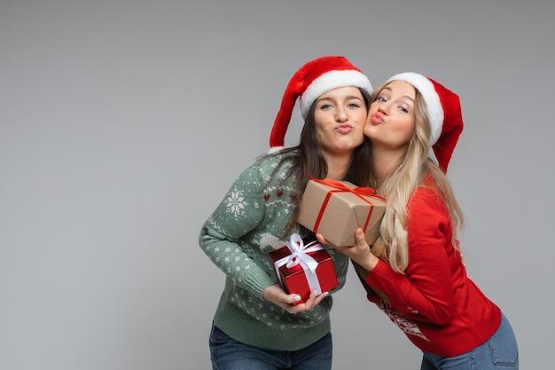 Vrolijke blanke zusters in warme groene en rode truien houden hun kerstcadeaus vast, foto geïsoleerd op een witte muur