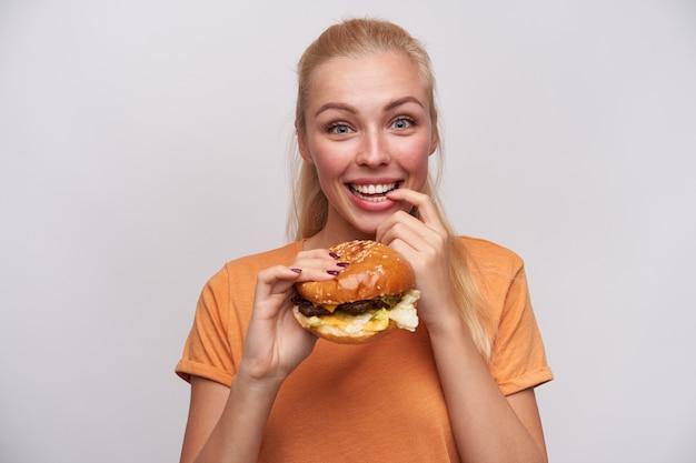 Vrolijke blauwogige jonge mooie blonde dame met casual kapsel opgewonden kijken naar de camera en verse hamburger in opgeheven hand houden, wijsvinger op onderlip houden en breed glimlachen