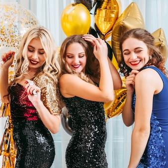 Vrolijke, blije dames in cocktailjurken met lovertjes die genieten van een feestelijke stemming, samen rondhangen, plezier maken, dansen.