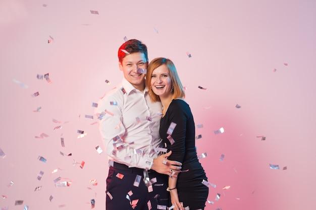 Vrolijke blije jonge mensen staan met vallende confetti